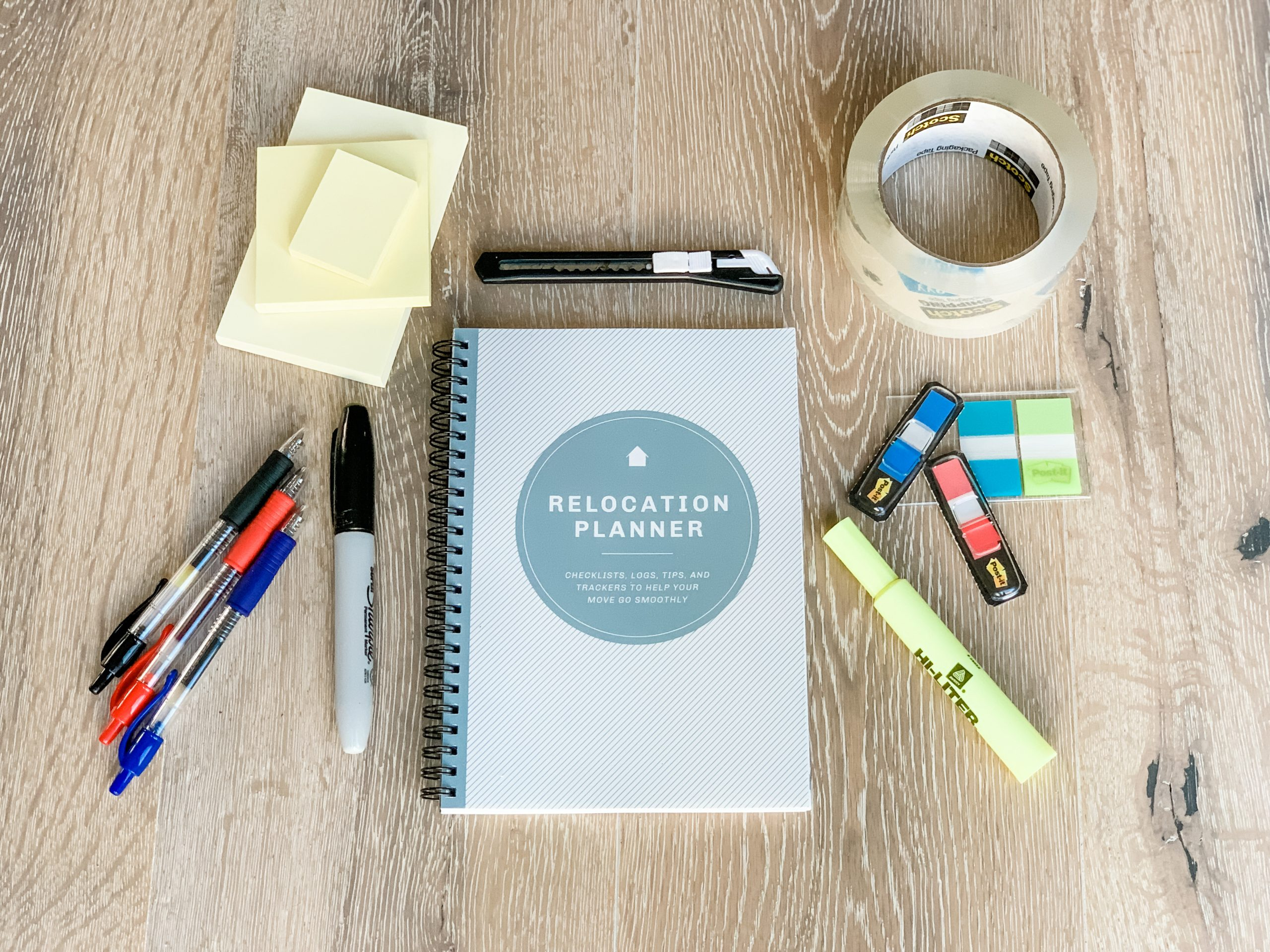 relocation planner surrounded by office supplies: tape, highlighters, markers, pens, post-it notes, box cutter, tape