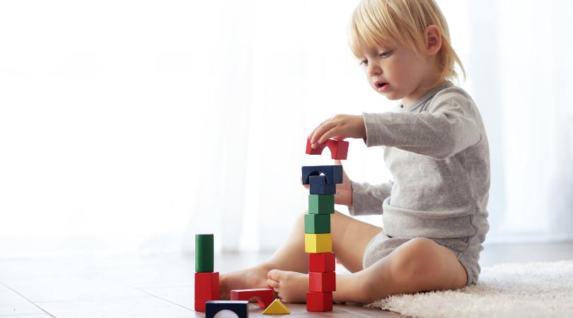 Blonde toddler sitting and stacking blocks