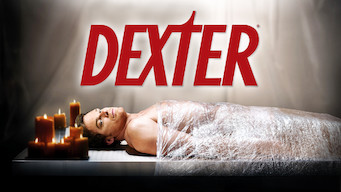 "A man lying down syran wrapped to a table. Numerous candles are lit around his head. Text overlay ""Dexter"""