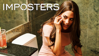 "A woman sitting on a toilet in a pink dress talking on the phone looking to the side.  Text overlay ""Imposters"" The Netflix logo is in the top left corner."
