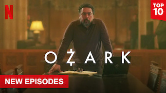 "A man standing at the end of a table with a computer and pad of paper in front of him.  A few men are in the background.  Text overlay ""Ozark"" The Netflix logo is in the top left corner."