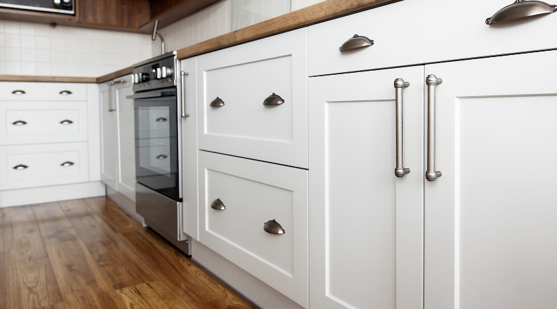 White lower cabinets in a kitchen and an oven