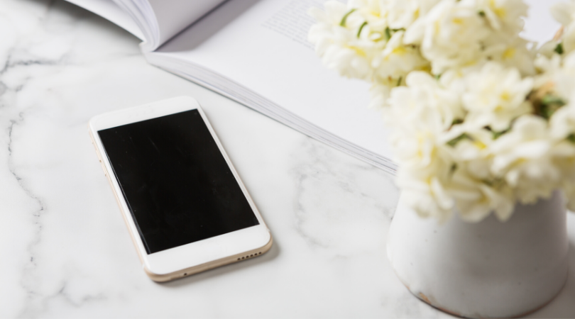 A white iPhone sitting on a marble counter next to an open book and a vase of white flowers