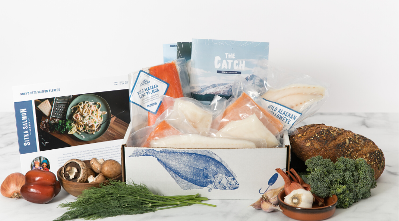 Box of flash frozen seafood with vegetables, a loaf of bread, and recipes next to it
