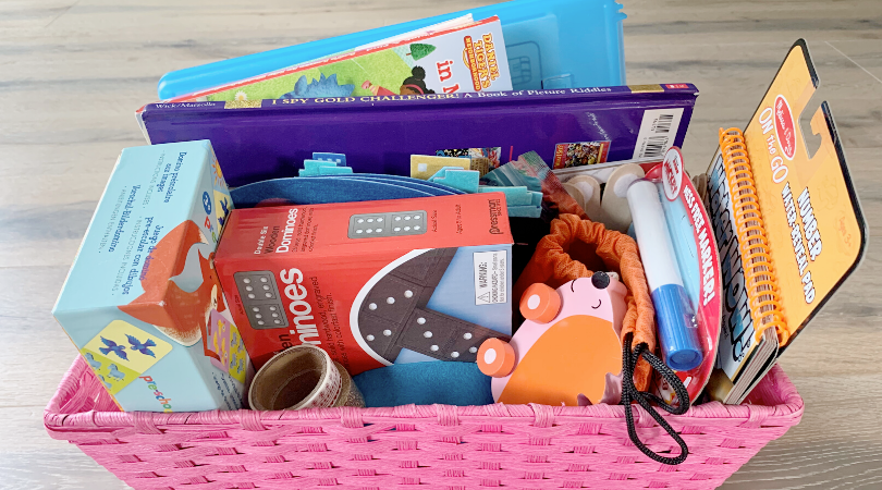 A pink basket of toys including dominoes, markers, and books.