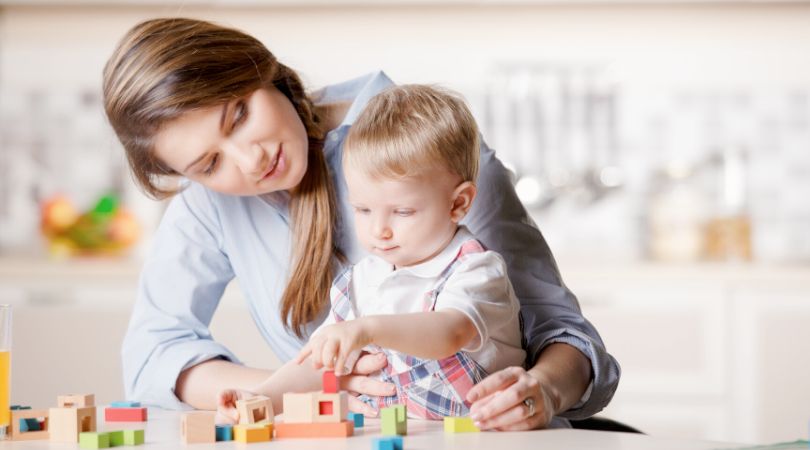 A woman with a toddler in her lap who is playing with blocks.