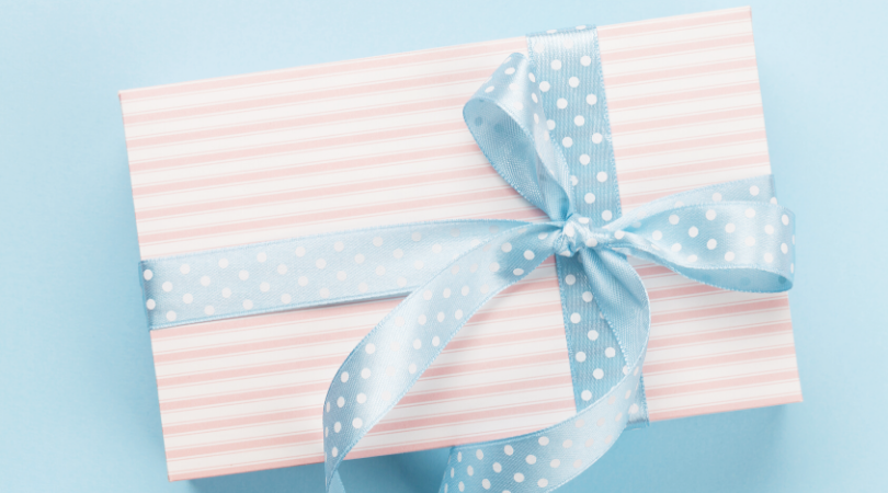 A rectangle present with pink and white striped wrapping paper with a light blue and white polka-dotted ribbon and bow.