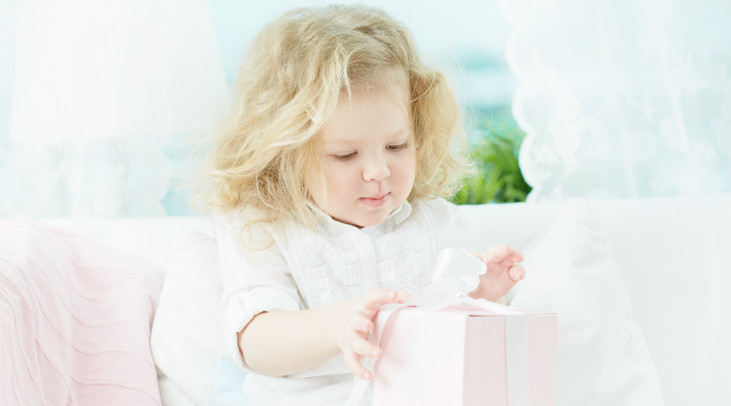 A toddler opening a pink present with a white ribbon attached