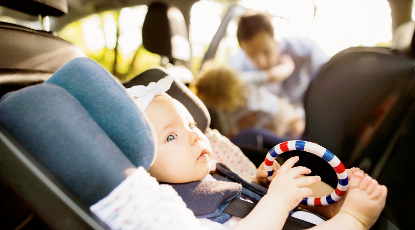 A baby holding a ring toy in a carseat, while an adult is putting in an older child in the carseat next to her.