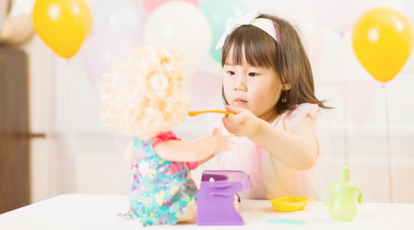 A toddler girl, with balloons in the background, feeding her baby doll with a spoon