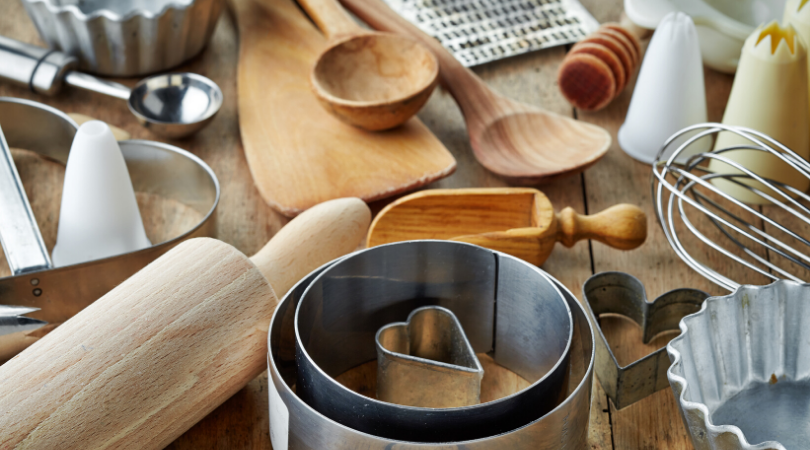 Collection of kitchen tools on a wooden counter, including but not limited to wooden spoons, rolling pins, whisk, cookie cutters