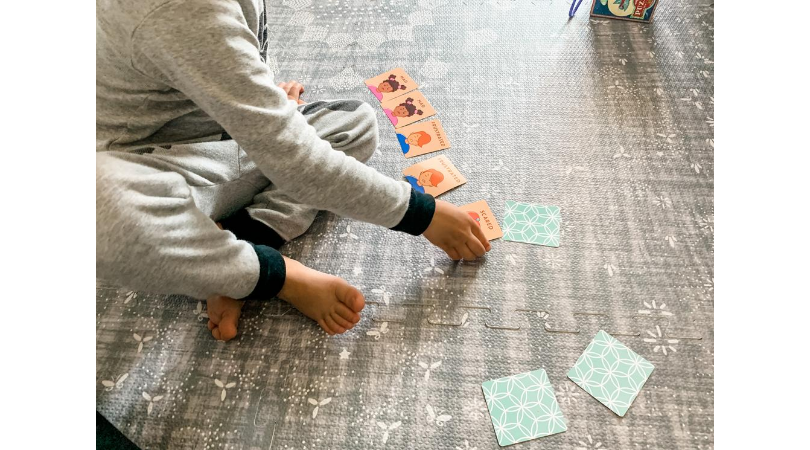 picture of toddler playing match card game with Generation Mindful emotion cards
