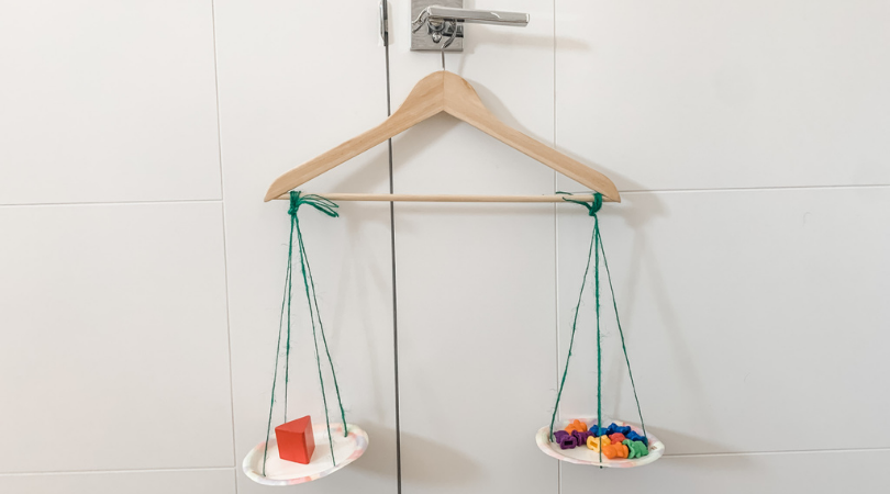 Homemade balance scale with hanger, string, and paper plates.  Measuring a wood triangle block and bears.