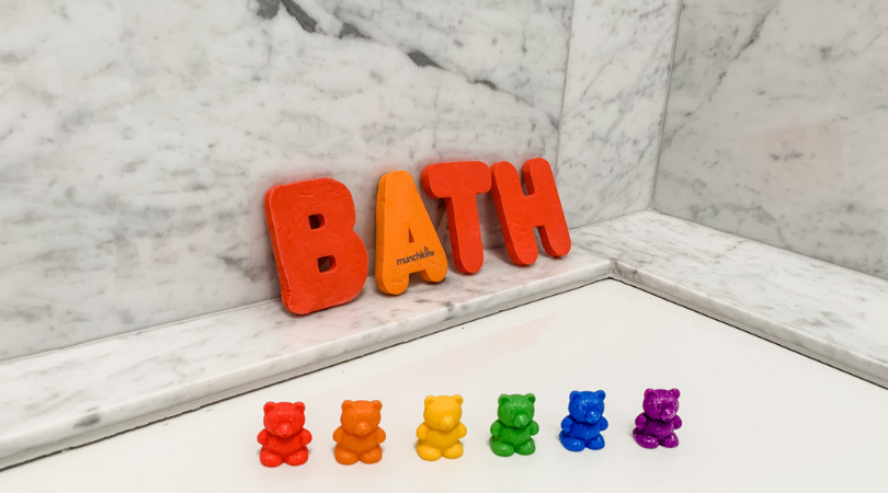 """Counting bears on the side of the bath with foam bath letters spelling """"Bath"""""""