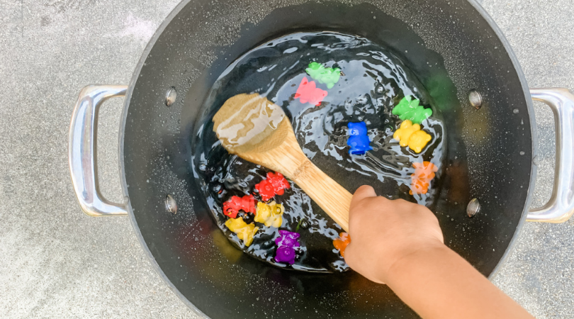 Pot full of water and counting bears being stirred with a wooden spoon by toddler