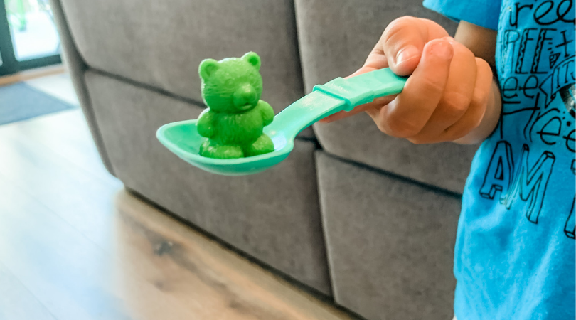 Toddler holding a teal spoon with a green bear