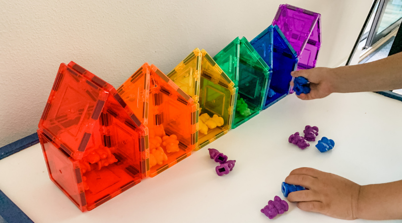 Magnetizes built into houses, in a rainbow color order.  Toddler sorting colored bears into corresponding houses.