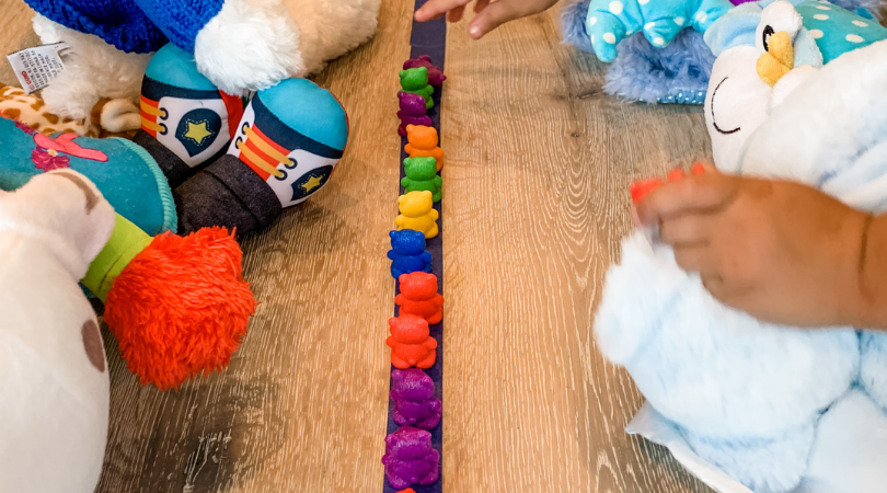 Counting bears lined up on a piece of blue tape.  Stuffed animals on each side.