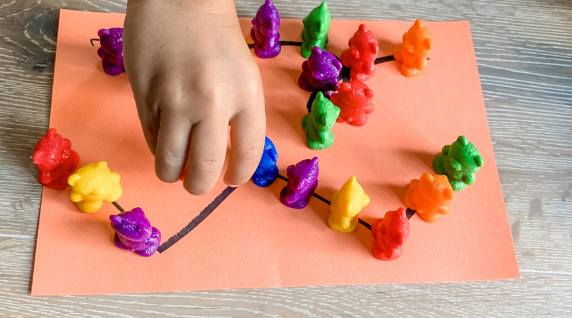 Toddler placing colored counting bears on an orange piece of paper with zig zag pattern