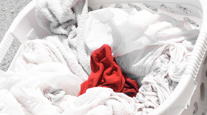 Basket of laundry with white linens and a red article of clothing