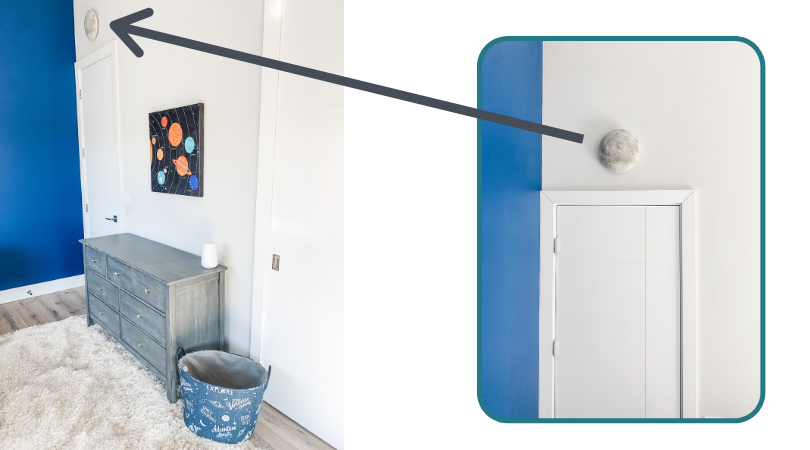 Two pictures.  The first is a wall with planet artwork, a moon lamp on.  Then a gray dresser and a blue hamper.  The second photo is an unclose photo of the moon lamp above the door.