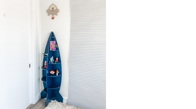 A blue rocketship bookshelf up against the wall with an alien clock above on the wall