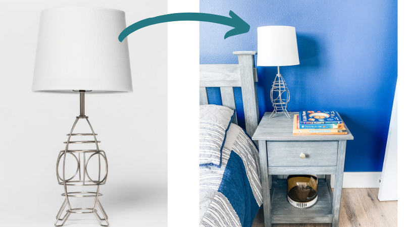 A gray nightstand with a rocketship lamp, space themed books on the top, and an astronaut hemet on the bottom