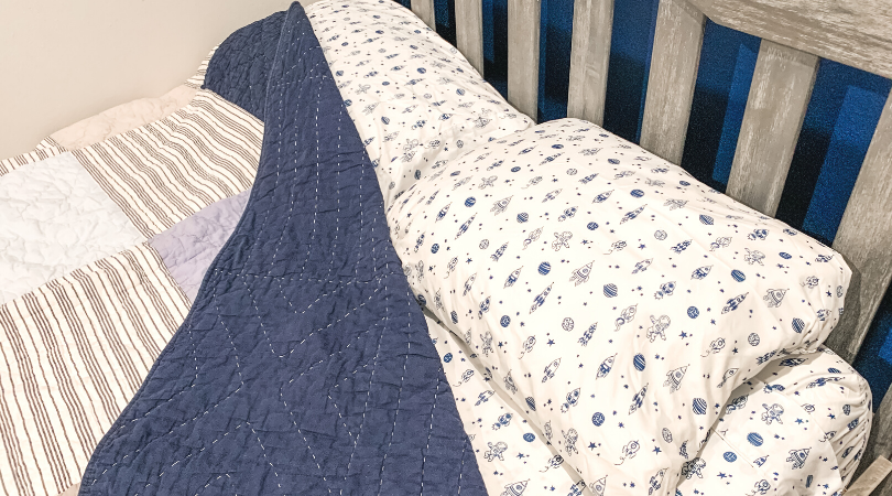 White and blue Rocketship sheets with a blue quilt